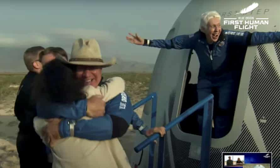 Wally Funk, right, wearing a blue jumpsuit, emerges from a capsule with a look of joy and her arms flung wide after the flight aboard Blue Origin's New Shepard rocket.
