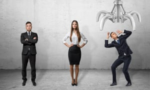 Confident business people standing straight and scared businessman shielding himselfA confident businessman and businesswoman standing straight and a scared businessman shielding himself with his hands from the giant mechanical claw above him, all on the grey background. Business and management. Recruitment and competition. Corporate culture.