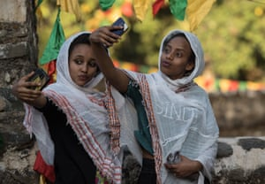 Women pose for a selfie during the celebration