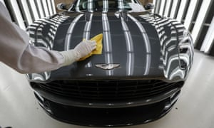 A man polishes an Aston Martin DB11