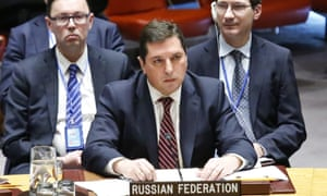 Vladimir Safronkov, centre, Russia's deputy UN ambassador, keeps his hand lowered during the vote.