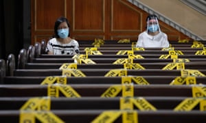 Women wearing protective masks kneel to pray in between social distancing markers placed on pews in St. Peter Parish, Metro Manila