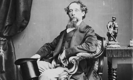 Charles Dickens formally posed, seated in an armchair  holding his top hat