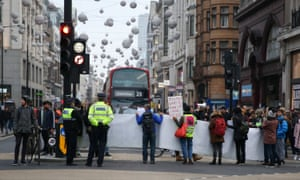 Protesters seen holding a huge banner during the protest blocking Oxford Street, London.