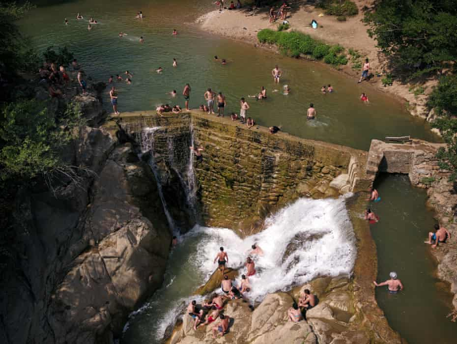 A man leaps from the wall of the Samtsvera waterfall, near Zestafoni, on a 38C day