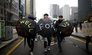 """Participants holding umbrellas with the message """"Well for us, Hell for earth"""" march in Seoul."""