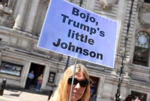 An anti-Boris Johnson protester holds up a sign after his announcement as Britain's next prime minister at the Queen Elizabeth II centre in London.