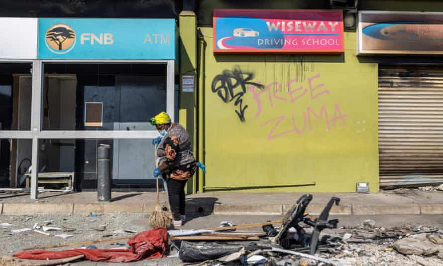 A woman clears debris from the street after violence and looting in Durban last week