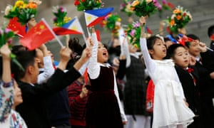 Chinese children cheer and wave Chinese and Philippines national flags and bouquets of flowers for the welcome ceremony for Rodrigo Duterte.