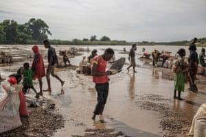 Malagasy workers seep soil through a strainer, in the waters of a river looking for gems, at an informal Sapphire mine