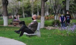 A man sits on a bench at a park in Wuhan