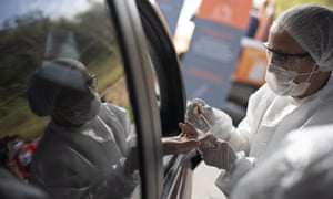 A health worker collects a blood sample at a drive-through test site in Niteroi, Brazil.