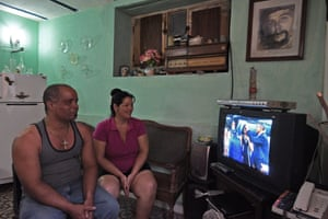 A Cuban family watch the arrival of Obama on TV