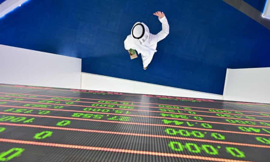 A trader walks beneath a display board at the Dubai Stock Exchange.