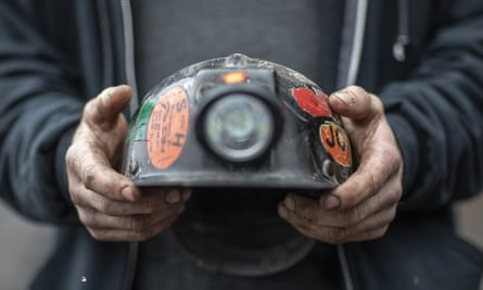 An employee of Quest Energy, holds his mining helmet near railroad tracks where miners, who say they have not been paid in nearly three weeks, block a coal train in the Kimper area of Pike county, Kentucky, in January.