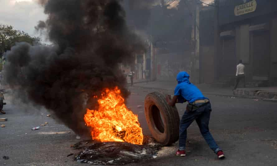A man rolls a flaming tire during clashes at the presidential palace in Port-au-Prince, Haiti, on 23 February.