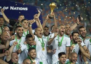 Algeria captain Riyad Mahrez lifts the trophy as his team celebrate.