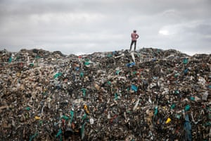 A man stands on top of a mountain of rubbish at the Dandora dump in Nairobi, Kenya