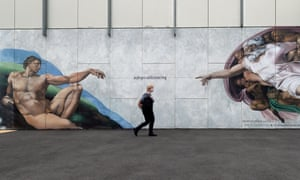 A woman passes under the words '#physicaldistancing' in a mural based on Michelangelo's The Creation of Adam in Melbourne, Australia.