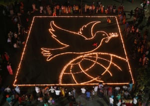 People light lamps to form a peace symbol on the eve of Diwali in Chandigarh, India
