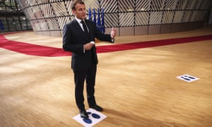 French President Emmanuel Macron makes a statement to the media as he stands on a physical distancing marker on arrival for an EU summit in Brussels, Sunday, July 19, 2020.