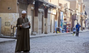 An Egyptian reads a newspaper in the neighborhood of El-Gamaliah, in Cairo, on Friday, the middle of a long weekend in the country.