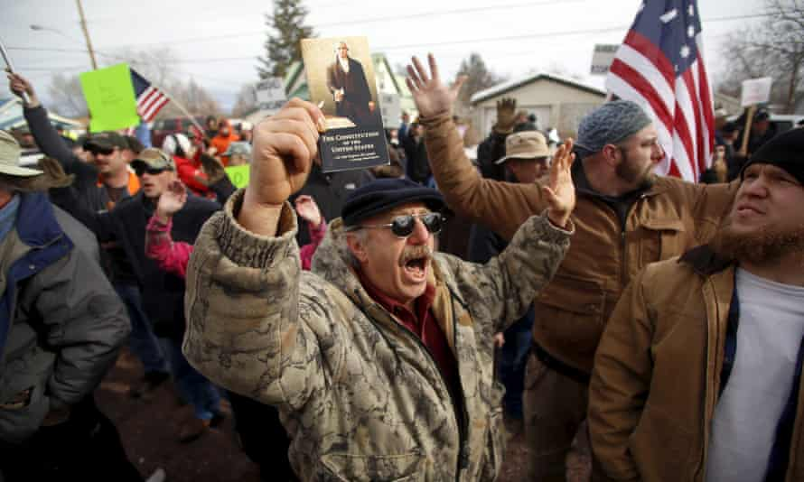 A pro-militia supporter holds a copy of the constitution while chanting during a protest outside the Harney County courthouse in Burns, Oregon.