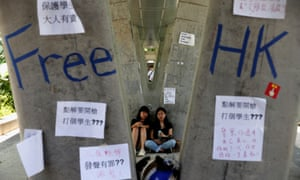 People sit next to posters and signs placed following protests against the proposed extradition bill, in Hong Kong