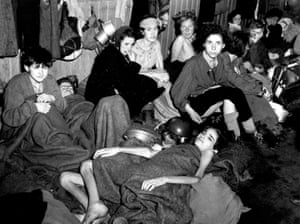 Liberated women and children prisoners at Bergen-Belsen huddle together in a barrack at the camp.