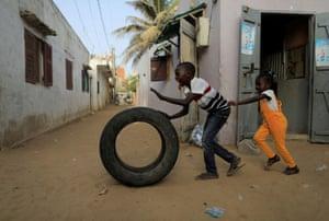 Dakar, Senegal: children play with a tyre in the Yoff neighbourhood