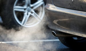An exhaust pipe of a car is pictured on a street in a Berlin, Germany
