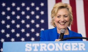 Hillary Clinton standing at a podium with the word 'stronger'. She is smiling and the US flag is behind her