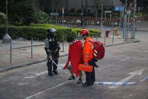 A riot policeman looks at a protester as he leaves the campus