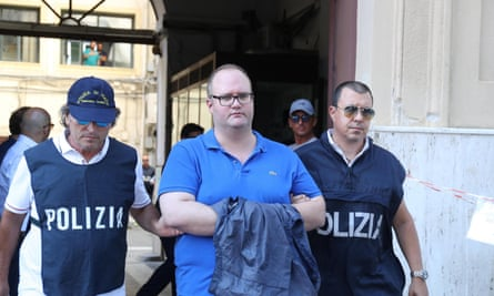 Two policemen arrest Salvatore Gambino in Palermo, Italy Wednesday.