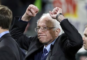 Bernie Sanders pumps his fists as he leaves the field after speaking at a rally in Seattle.