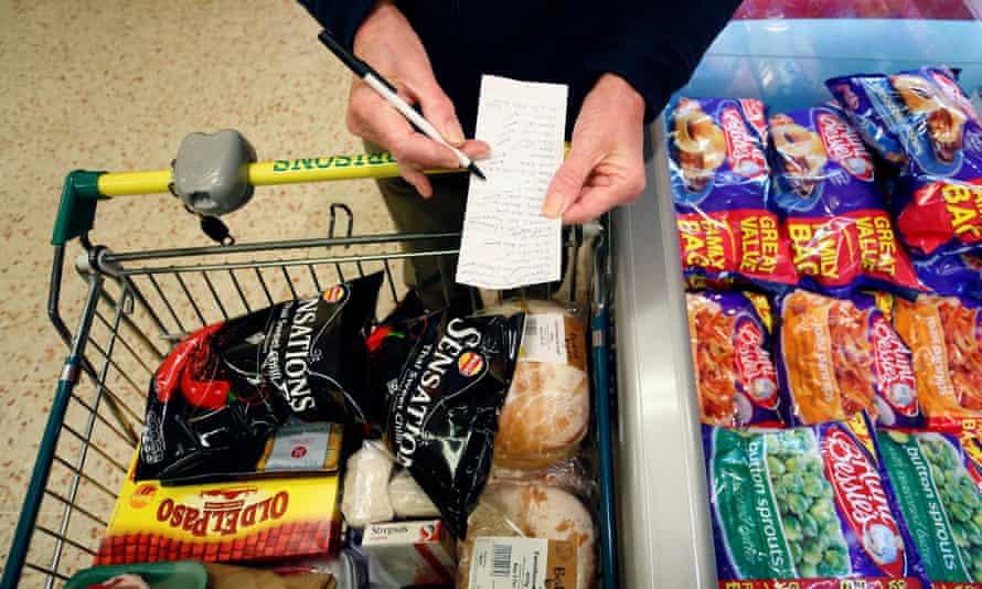 A customer checks their shopping list inside a Morrisons supermarket.