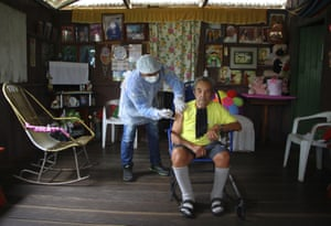 Elfiginio Euzebio de Matos, 93, right, receives a dose of the Oxford-AstraZeneca Covid-19 vaccine from a healthcare worker in the Mabedery community along the Purus Rriver, in the Labrea municipality, Amazonas state, Brazil, Friday, on 12 February, 2021.