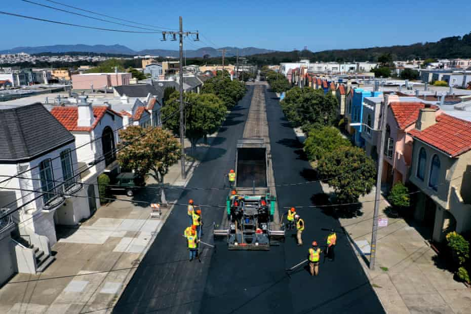 Workers with the San Francisco Department of Public Works repave a section of 24th Avenue.