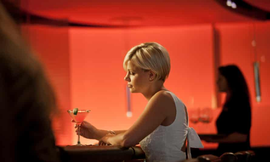 A woman alone at a bar with a drink posed by model