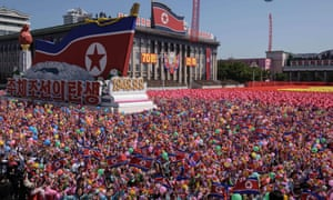 Participants wave flowers as they march past a balcony from where North Korea's leader Kim Jong-un was watching.