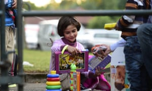 A young refugee girl plays with game she received upon arrrival at a former Fire station in Celle, northern Germany