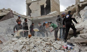 Rescuers and civilians inspect a destroyed building in the Syrian village of Kfar Jales following airstrikes by Syrian and Russian warplanes.