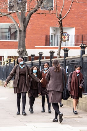 Students of Notre Dame secondary school walk out from the building after the first day at school in southern London as schools in England reopen on 8 March, 2021.