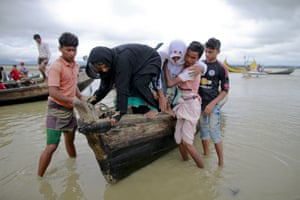 Bangladeshi villagers help two elderly Rohingya women get down from a boat after crossing a canal at Shah Porir Deep, in Teknaf