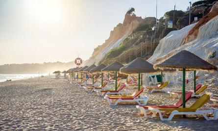 Colourful sun beds under straw umbrellas on Falesia Beach, Albufeira, Algarve, Portugal