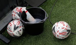 Balls wait to be cleaned in a bucket of disinfectant at Carrow Road.