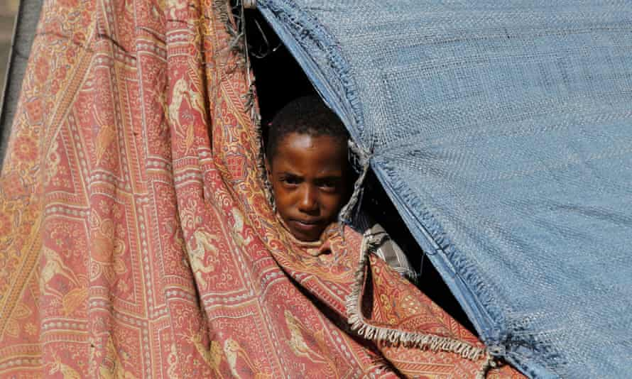 A young Yemeni forced to flee their home due to ongoing fighting peers through a gap in a makeshift tent at a displaced person's camp in the country's Amran province.