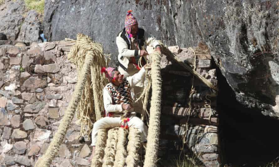 I membri della comunità Huinchiri utilizzano tecniche di tessitura tradizionali per ricostruire il ponte sospeso a Canas, in Perù, il 13 giugno 2021.