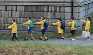 Students keeping their distance arrive at elementary school in Milan, Italy, for the first day of term.