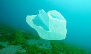 plastic waste floating under water,